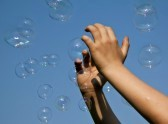 8038775-hands-catching-bubbles-against-a-blue-sky-in-sunshine